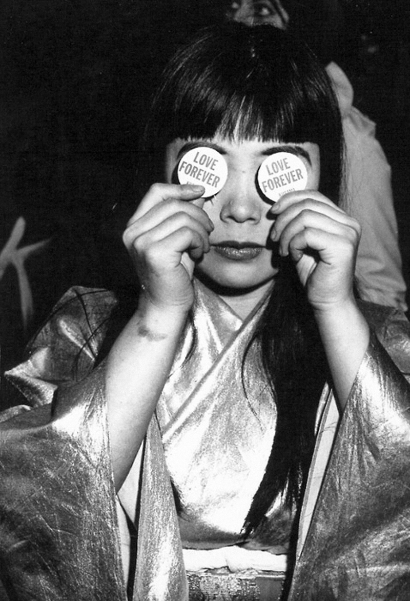 "YAYOI KUSAMA with ""LOVE FOREVER"" buttons, which she distributed at the opening of Kusama's PEEP SHOW, a mirror-lined environmental installation at Castellane Gallery. New York, 1966. Photograph by Hal Reiff. Image courtesy: Ota Fine Arts, Tokyo / © Yayoi Kusama, Yayoi Kusama Studio Inc."