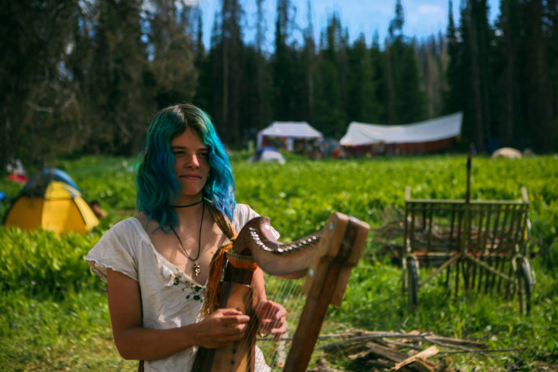A girl playing the harp at the Rainbow Gathering in the Uinta National Forest, Utah, USA. Photo Tyler Coleman.