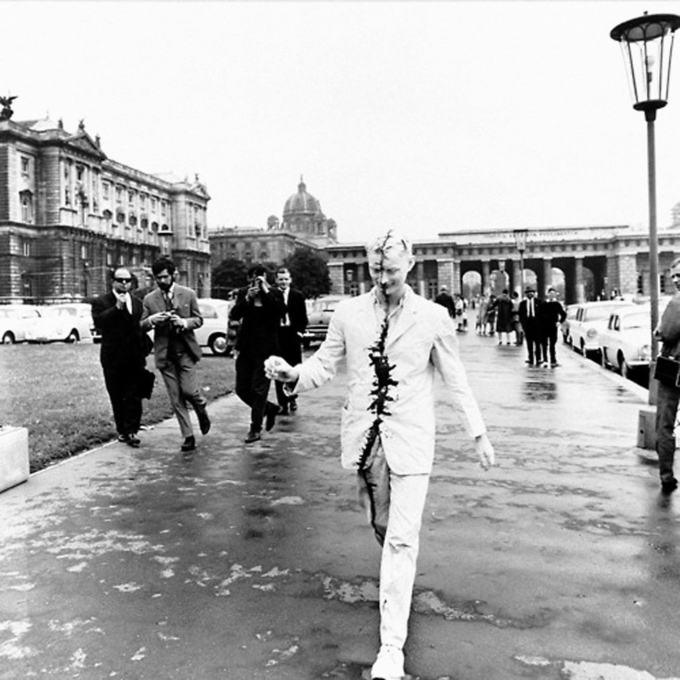 Artist Günter Brus strolling through the centre of Vienna in Austria the day after his first public action, 'Self-Painting/Self-Mutilation' in 1965. Painted entirely in white with a black strip over his face and body, Brus was almost immediately arrested by the police for being potentially disturbing to the public (as noted by Tracey Warr and Amelia Jones in The Artist's Body)