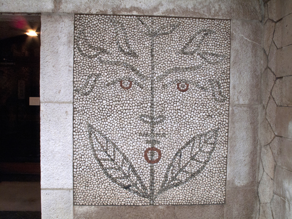 A faun man in Cocteau's pebble mosaic outside the Bastion Museum.