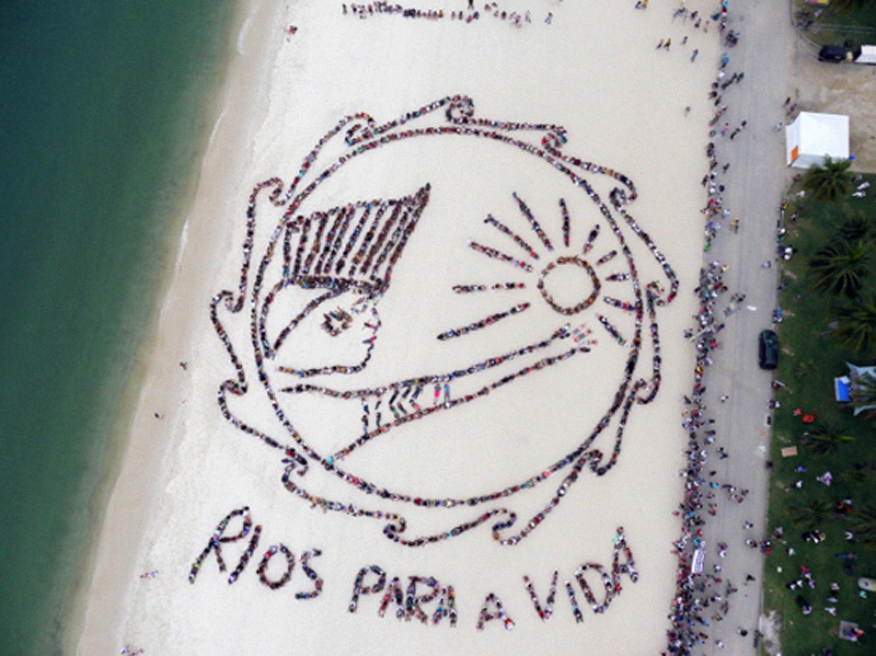 RIVERS FOR LIFE: A living art work using Rio de Janeiro's Flamengo Beach as a canvas. The image was an artistic collaboration between world-renowned aerial artist John Quigley and a visionary committee of indigenous peoples including Aldamir Sataré-Mawé (Amapá), Sheyla Juruna (Pará), Dione Vison Terena (Mato Groso do Sul), Augusto Kaigamg (Rio Grande do Sul), and Capitao Potuguara; June 2012.