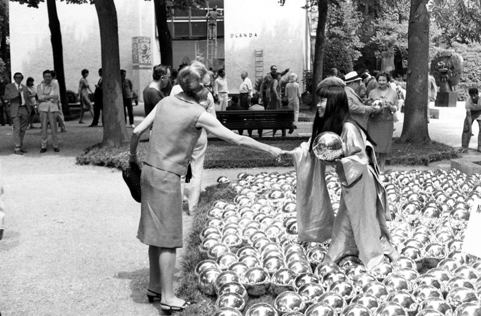 YAYOI KUSAMA with NARCISSUS GARDEN, Venice Biennale, 1966. Kusama offered the 1,500 mirrored balls for sale at 1200 lire ($2 each). She was prohibited from doing this and gave out leaflets praising her own work as she had crashed event wearing a golden kimono. Image courtesy: Ota Fine Arts, Tokyo / © Yayoi Kusama, Yayoi Kusama Studio Inc.