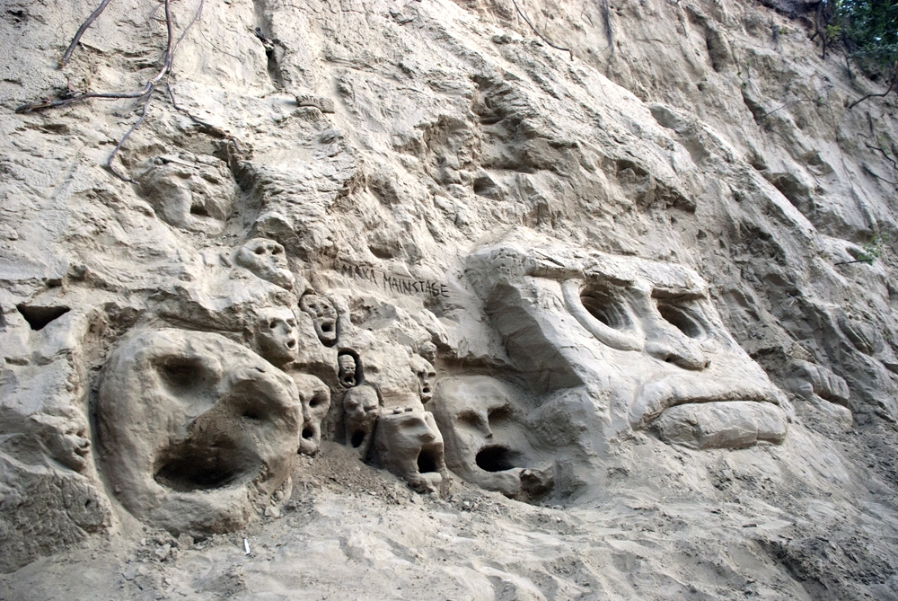A mysterious growth of faces and masks in the rock.