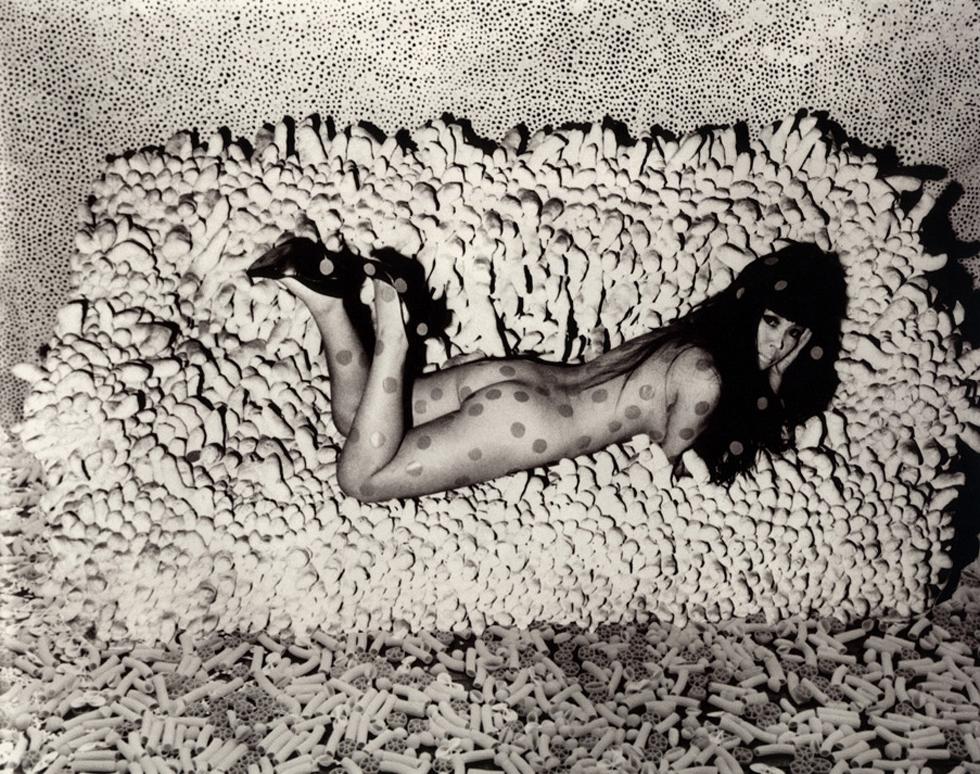 YAYOI KUSAMA, photographed by Hal Reif reclining on  her work ACCUMULATION (1963-4): Accumulation No.2, Infinity Net and macaroni carpet in the background. Image courtesy: Ota Fine Arts, Tokyo / © Yayoi Kusama, Yayoi Kusama Studio Inc.