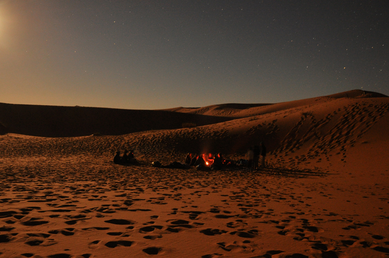 Moonrise at night in the desert, in the left foreground of the camp.