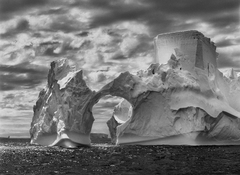 Iceberg between Paulet Island and the South Shetland Islands on the ANTARCTIC Channel. At sea level, earlier flotation levels are clearly visible where the ice has been polished by the ocean's constant movement. High above, a shape resembling a castle tower has been carved by wind erosion and detached pieces of ice. The Antarctic Peninsula, 2005.